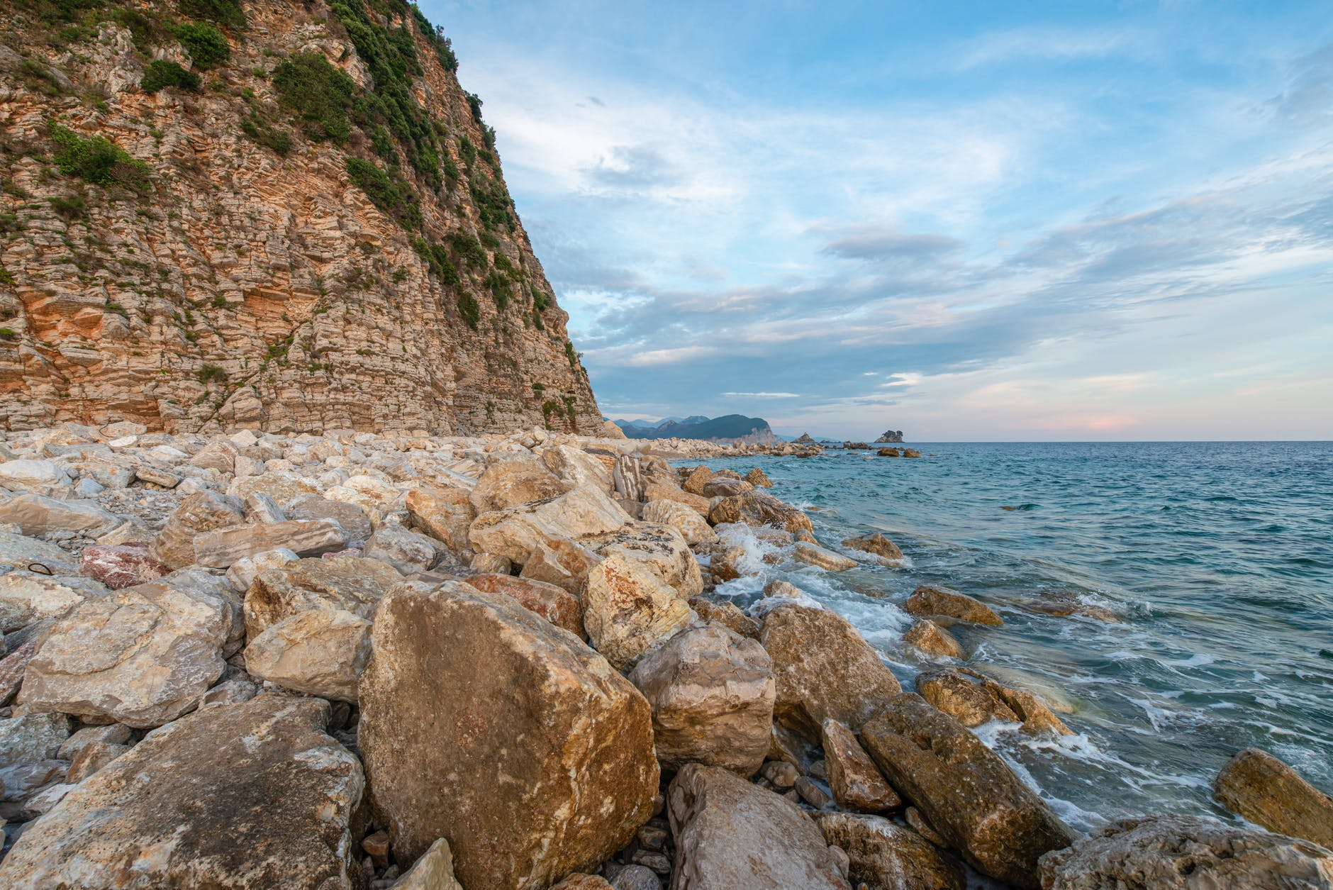cliff surrounded with heavy rough stones washed by ocean